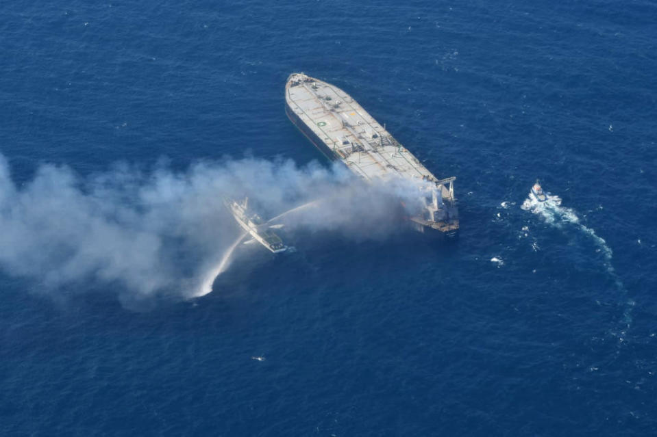 In this photo provided by Sri Lanka Air Force, a ship battles the fire on MT New Diamond, off the eastern coast of Sri Lanka in the Indian Ocean,, Saturday, Sept. 5, 2020. The fire on the large oil tanker off Sri Lanka's coast has been brought under control but is still not extinguished, the navy said Saturday. The tanker, carrying nearly 2 million barrels of crude oil, was drifting about 20 nautical miles (37 kilometers) from Sri Lanka's eastern coast and on Friday evening a tug boat towed it to the deep sea away from land, said navy spokesman Capt. Indika de Silva. (Sri Lanka Air Force via AP)