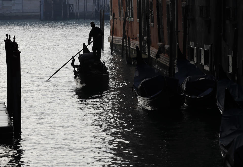 A gondolier navigates the waterways in Venice, Italy, Saturday, Jan. 30, 2021. Gondolas and other vessels are moored instead of preparing for Carnival's popular boat parade in the lagoon. Alleys are eerily empty. Venetians and the city's few visitors stroll must be masked in public places, indoors and out, under a nationwide mandate. (AP Photo/Antonio Calanni)