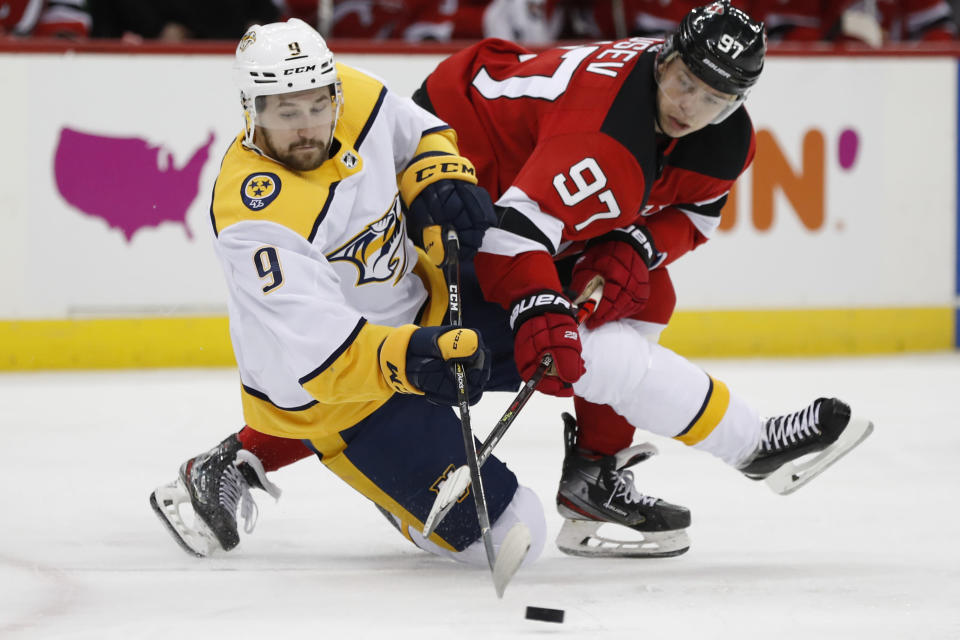 New Jersey Devils left wing Nikita Gusev (97), of Russia, and Nashville Predators left wing Filip Forsberg (9), of Sweden, go after the puck as Forsberg falls to the ice during the second period of an NHL hockey game, Thursday, Jan. 30, 2020, in Newark, N.J. (AP Photo/Kathy Willens)