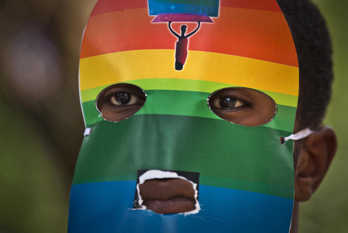 """FILE - In this Monday, Feb. 10, 2014 file photo, a Kenyan gay wears a mask to preserve his anonymity as they stage a rare protest, against Uganda's increasingly tough stance against homosexuality and in solidarity with their counterparts there, outside the Uganda High Commission in Nairobi, Kenya Monday, Feb. 10, 2014. Ugandan President Yoweri Museveni met in his office with a team of U.S.-based rights activists concerned about legislation that would impose life sentences for some homosexual acts and made clear he had no plans to sign the bill, according to Santiago Canton of the Robert F. Kennedy Center for Justice and Human Rights who attended the Jan. 18, 2014 meeting, but one month later Museveni appears to have changed his mind, saying through a spokesman in February 2014 that he would sign the bill """"to protect Ugandans from social deviants."""" (AP Photo/Ben Curtis, File)"""