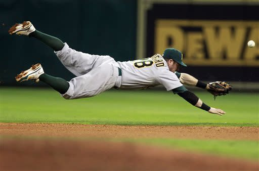 Oakland Athletics second baseman Eric Sogard dives for a Houston Astros' Robbie Grossman single to right field in the seventh inning during a baseball game on Saturday, May 25, 2013, in Houston. (AP Photo/Patric Schneider)
