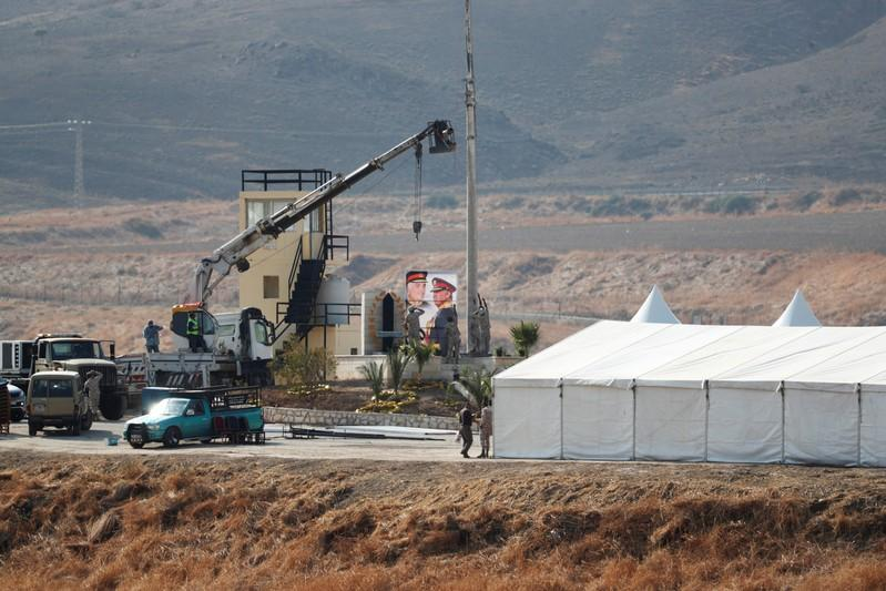 """Jordanian soldiers prepare to raise the Jordanian national flag near a tent at the """"Island of Peace"""" in an area known as Naharayim in Hebrew and Baquora in Arabic, on the Jordanian side of the border with Israel, as seen from the Israeli side"""