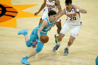 Charlotte Hornets guard LaMelo Ball (2) drives as Phoenix Suns forward Dario Saric (20) defends during the first half of an NBA basketball game, Wednesday, Feb. 24, 2021, in Phoenix. (AP Photo/Matt York)