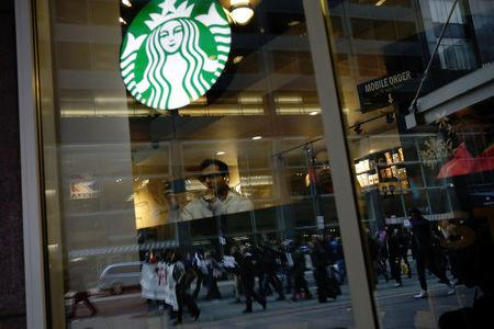 Protesters marching down Market Street are seen reflected in a Starbucks storefront in Philadelphia, a week after two black men were arrested at a Starbucks coffee shop, in Philadelphia, Pennsylvania, U.S. April 19, 2018.  REUTERS/Dominick Reuter