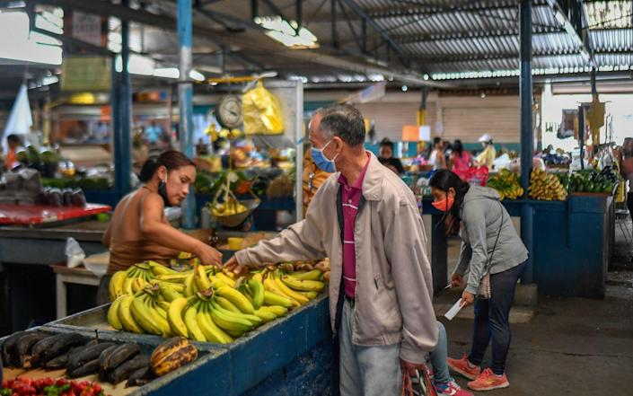 A man buy bananas at the municipal market of Chacao in Caracas amid the COVID-19 novel coronavirus pandemic - FEDERICO PARRA /AFP
