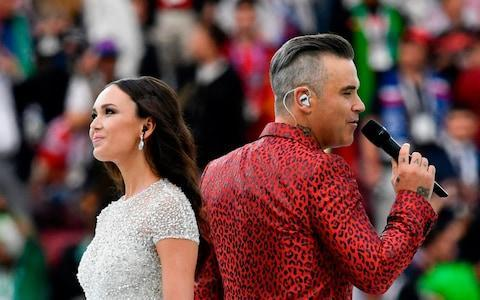 "England probably won't win the football tournament but at least a bloke from Stoke-on-Trent was the star of the curtain-raising event. Before a ball was kicked, Robbie Williams worked the crowd and crooned karaoke-style at the Fifa World Cup 2018: Opening Ceremony (ITV). Port Vale 1, Rest of the World 0. Marking the start of the 21st global football feast, Williams swaggered cockily into Moscow's 80,000-seat Luzhniki Stadium wearing a red leopardskin suit, as if Morrissey had gone to Las Vegas, and launched into a medley of his hits: Let Me Entertain You (at least its lyrics fitted the occasion), Feel and Angels (the latter two, not so much). Sadly, there was no Party Like a Russian, the 2016 single that reportedly ruffled feathers with its Kremlin-baiting lyrics. In the run-up to this gig, the former Take That favourite had been accused of ""selling his soul"" to Vladimir Putin. Talking of which, Williams has also reportedly signed up to join talent show oligarch Simon Cowell on The X Factor judging panel. Dancers were fearsomely drilled, with rictus smiles and sparkly tracksuits. Others had footballs on their heads and hopped around like Teletubbies. Gymnasts, jugglers, trampolinists and flaming torches added to the circus atmosphere, with Williams as its eyebrow-waggling ringmaster. He was accompanied on Angels by celebrated Russian soprano Aida Garifullina, who arrived on the back of a giant papier maché firebird. Sadly, TV cameras missed the big moment when its wings spread to reveal her. Russian soprano Aida Garifullina flies into the stadium Credit: Sergei Bobylev We were treated to the surreal sight of Ronaldo, a two-time World Cup winner with Brazil, high-fiving a wolf. The lupine interloper was official mascot Zabivaka, who bore a worrying resemblance to Noel Edmonds. The crowd's delirious reaction might have been connected to the fact that Putin was present to give a welcome speech. Mercifully brief at a mere 10 minutes, this was less like Danny Boyle's London 2012 extravaganza, which has set an impossibly high bar for such ceremonies, and more akin to a stadium Super Bowl half-time show or Eurovision performance. All that was missing was sardonic commentary from Graham Norton. Williams and Russian soprano Aida Garifullina Credit: Alexander Nemenov ITV cut away from the festivities at the earliest opportunity, denying viewers the chance to watch Williams belt out Rock DJ while the stage was dismantled behind him in time for kick-off. However, he was captured by a Fox network camera raising his middle finger, an act lacking in class with so many children watching. Mark Pougatch helmed coverage from ITV's purpose-built studio in Red Square, where the fever dream decor made it appear like he was inside a giant Fabergé egg. Pougatch remained professional (except one fleeting reference to ""Saudia Arabe"") and was joined by four pundits, which was at least one too many. Blokey banter was the order of the day, with the women - reporter Jacqui Oatley and pundit Eni Aluko - relegated to pitch-side duties inside the stadium. A dancer looks on during the opening ceremony Credit: Matthias Hangst The early tone was a tad too morose, thanks to talk of the tournament's political context (pity poor Lee Dixon having to field that one as the first question) and a navel-gazing interview with England whipping boy Raheem Sterling. Once conversation turned to Love Island and Williams' performance was out of the way, the mood picked up. Finger aside, Williams did a decent job. There were no faux-pas, pratfalls or embarrassing protests but this felt like an apologetic, even cursory start. Let's hope the next four weeks of football are of a higher standard."