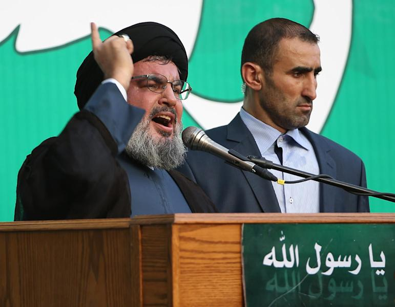 """Hezbollah leader Sheik Hassan Nasrallah, left, speaks to a crowd of tens of thousands of supporters, not shown, during a rally denouncing an anti-Islam film that has provoked a week of unrest in Muslim countries worldwide, in the southern suburb of Beirut, Lebanon, Monday Sept. 17, 2012. Nasrallah who does not usually appear in public for fear of assassination called for Monday's protests in Beirut, saying the U.S. must be held accountable for the film because it was produced in America. Arabic reads, """"the messenger of God."""" (AP Photo/Hussein Malla)"""