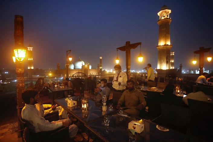 """People eat at a rooftop restaurant close to the historical Badshahi Mosque, on Aug. 11, 2020. <p class=""""copyright"""">AP Photo/K.M. Chaudary</p>"""
