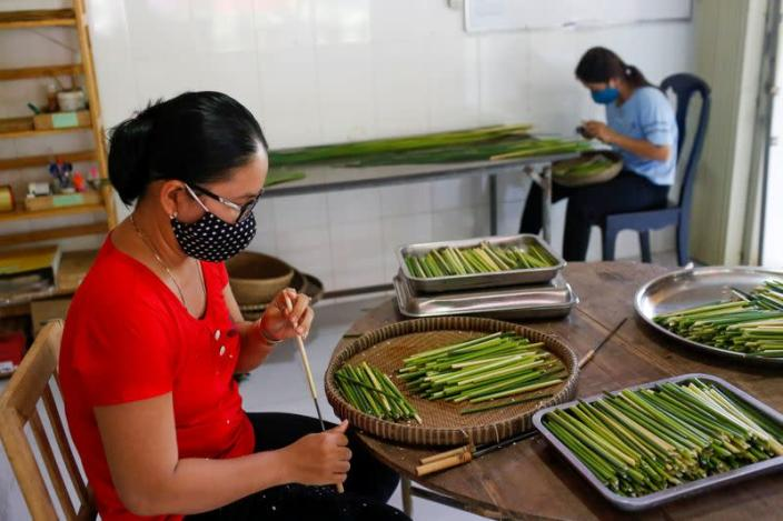 Workers make straws from grass at the 3T workshop in Long An province