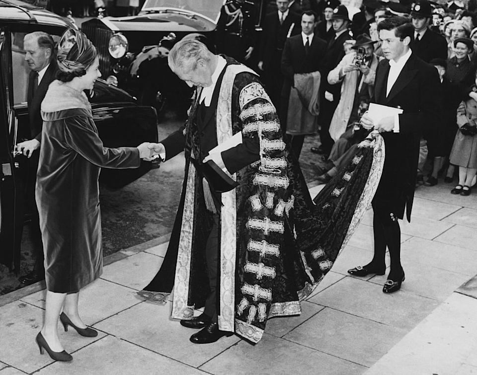 Queen Elizabeth II meets British Prime Minister Harold Macmillan (1894 - 1986), Chancellor of Oxford University, outside the Clarendon Building during a visit to Oxford, 4th November 1960. The PM's pageboy is his grandson Alexander Macmillan, later the 2nd Earl of Stockton. (Photo by Terry Disney/Central Press/Getty Images)