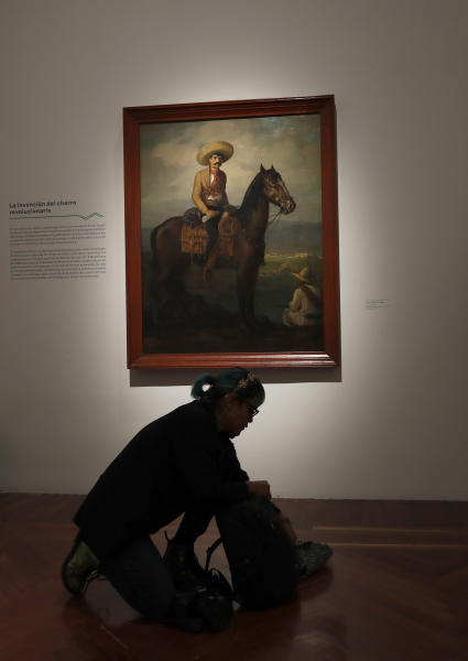 A journalist packs her backpack below a portrait of Mexican revolutionary hero Emiliano Zapata by Jose Atanasio Monroy, displayed during an exhibit remembering the one hundred anniversary of the death of Zapata, at the Bellas Artes Palace museum in Mexico City, Tuesday, Nov. 26, 2019. The exhibit features 140 art pieces and objects that belonged to Zapata. (AP Photo/Marco Ugarte)