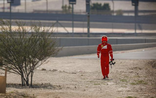 Raikkonen trudges off after his car stopped in first practice - Rex Features