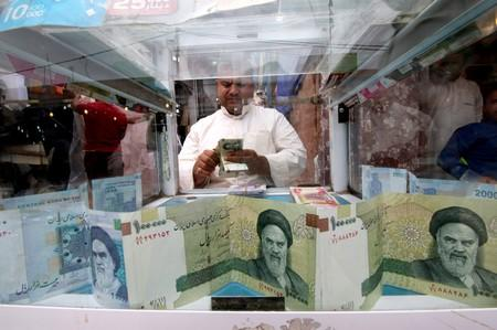 FILE PHOTO: A man counts Iranian rials at a currency exchange shop, before the start of the U.S. sanctions on Tehran, in Basra