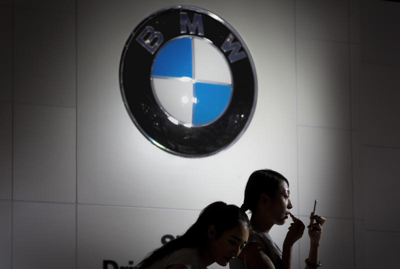 FILE - In this file photo dated Friday, Sept. 25, 2015, Models prepare to work at the BMW booth during the Imported Auto Expo in Beijing, China. Automaker BMW said Monday July 9, 2018, it will have to raise prices on the U.S.-built SUVs it sells in China due to 40 percent import tax on cars from the United States, in retaliation for higher tariffs on Chinese goods imposed by President Donald Trump.(AP Photo/Andy Wong, FILE)