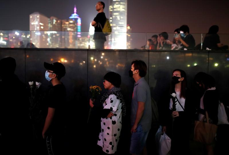 People line up to pay tribute at Tamar Park, outside the Legislative Council (Legco) building, during a prayer and remembrance ceremony in Hong Kong