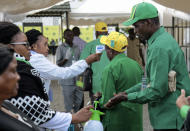 FILE - In this July 11, 2020, file photo, party members have their temperature checked and sanitize their hands as a precaution against the coronavirus at the national congress of the ruling Chama cha Mapinduzi (CCM) party in Dodoma, Tanzania. Tanzania's President John Magufuli openly expressed doubt about COVID-19 vaccines and accused people who were vaccinated outside the East African nation of bringing new infections into the country. (AP Photo/File)