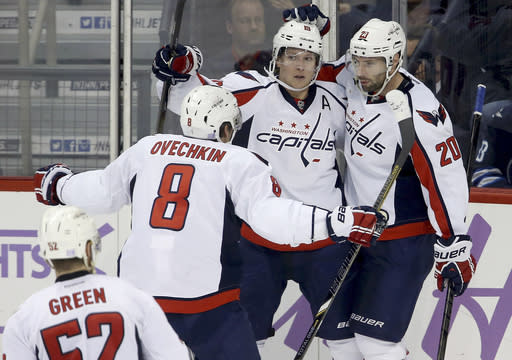 Washington Capitals' Mike Green (52), Alex Ovechkin (8), Nicklas Backstrom (19), and Troy Brouwer (20) celebrate Brouwer's goal during the third period of an NHL hockey game against the Winnipeg Jets in Winnipeg, Manitoba, Tuesday, Oct. 22, 2013. (AP Photo/The Canadian Press, Trevor Hagan)