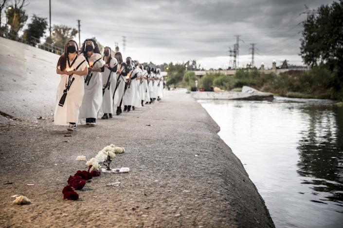 Artists dressed in white carry candles as they march along the banks of the river, where someone has placed flowers
