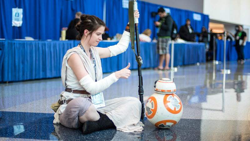 A cosplayer dressed up as Rey from Star Wars gives the thumbs up to a BB-8 drone