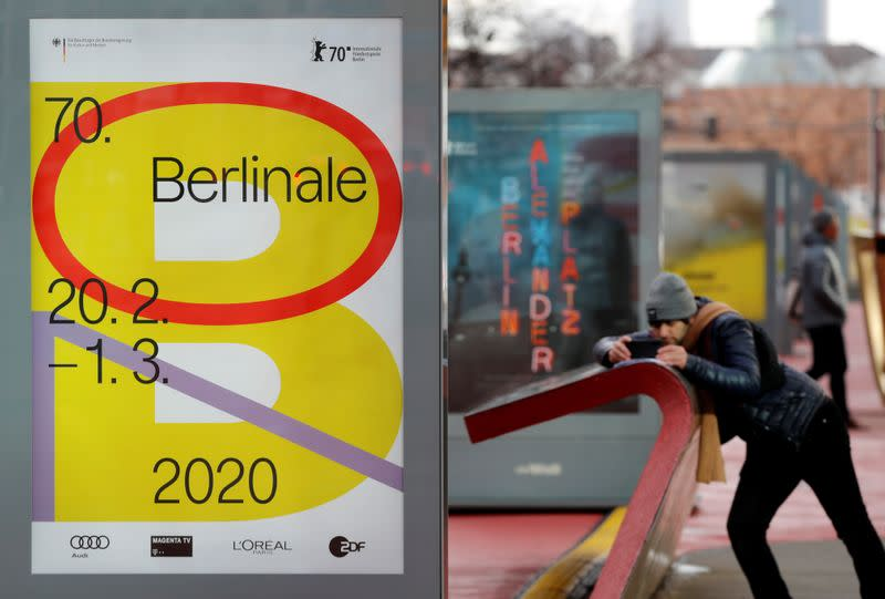 A pedestrian walks past an advertising billboard for the upcoming 70th Berlinale International Film Festival in Berlin
