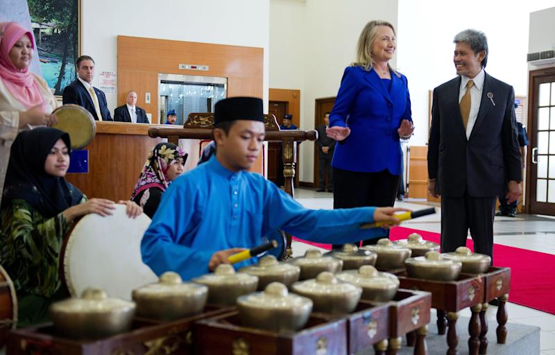 U.S. Secretary of State Hillary Rodham Clinton, second right, does a little dance next to Brunei's Foreign Minister Prince Mohamed Bolkiah as they arrive at Universiti Brunei Daussalam in Bandar Seri Begawan, Brunei, Friday, Sept. 7, 2012. (AP Photo/Jim Watson, Pool)