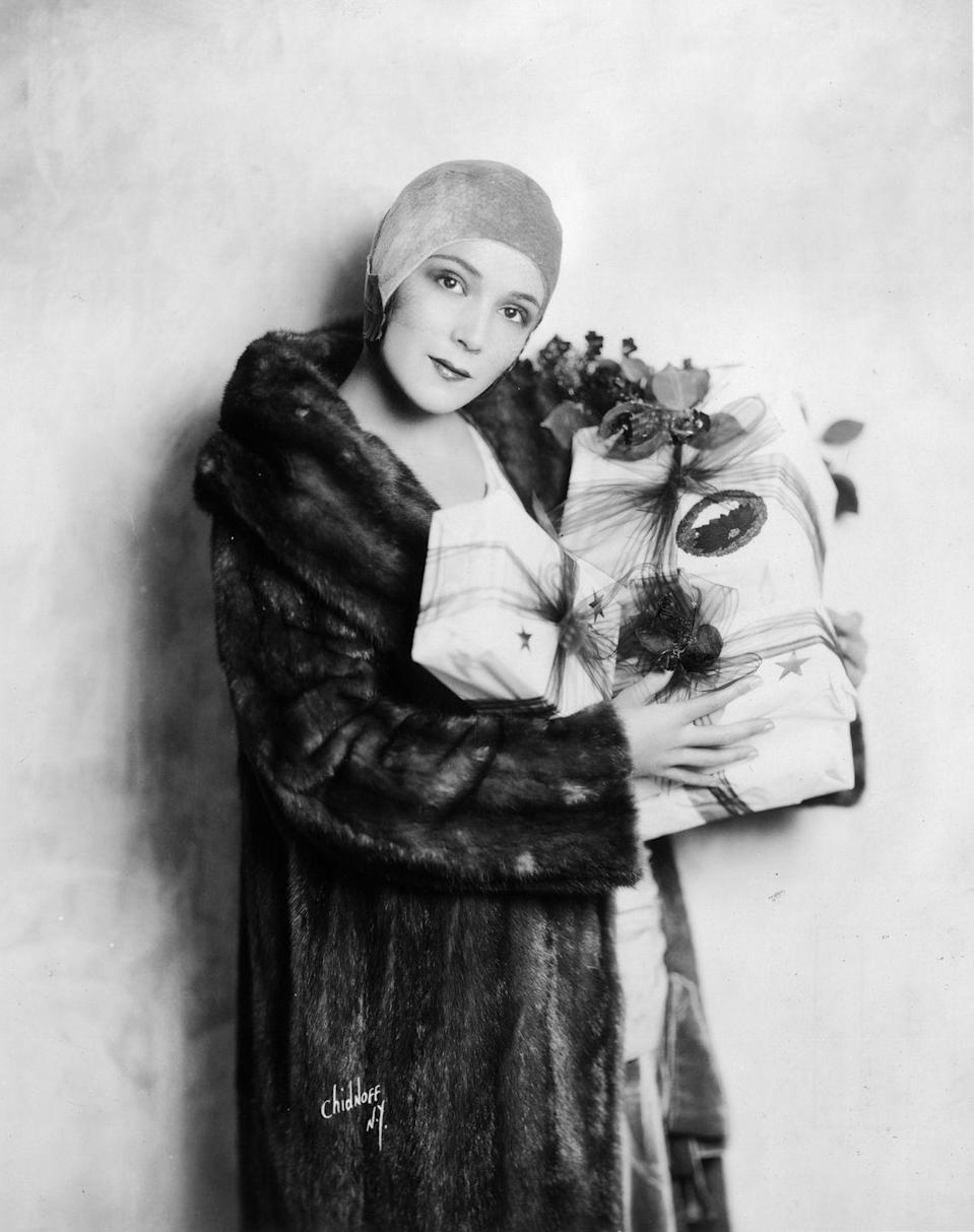 <p>Silent film star, Dolores Del Río, wears a mink fur coat and carries presents in 1925. The Mexican actress decorated her parcels with tulle ribbon and festive holly sprigs. </p>