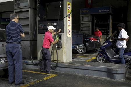 A worker handles the nozzle of a fuel dispenser at a gas station in Caracas
