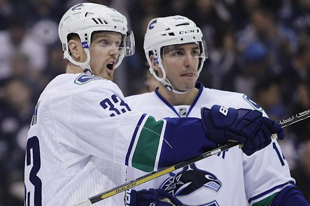 Vancouver Canucks' Henrik Sedin (33) and Alexandre Burrows (14) work out positions during the second period of an NHL hockey game against the Winnipeg Jets on Wednesday, March 12, 2014, in Winnipeg, Manitoba. (AP Photo/The Canadian Press, John Woods)