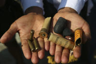 A protester show bullets, shotgun shells and rubber bullets used by security forces during a demonstration against the military coup in Mandalay, Myanmar, Friday, Feb. 26, 2021. (AP Photo)