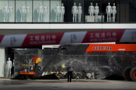 A worker sprays water near mannequins on display at a new Uniqlo clothing store at a newly constructed shopping mall in Beijing, Wednesday, Oct. 13, 2021. China's import and export growth slowed in September amid shipping bottlenecks and other disruptions combined with coronavirus outbreaks. (AP Photo/Andy Wong)