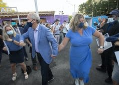O'Toole holds hands with his wife who wears a blue dress.