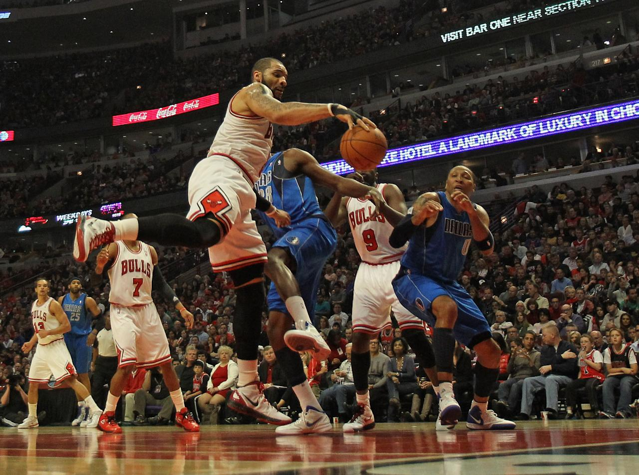 CHICAGO, IL - APRIL 21: Carlos Boozer #5 of the Chicago Bulls grabs a rebound against Ian Mahinmi #28 and Shawn Marion #0 of the Dallas Mavericks at the United Center on April 21, 2012 in Chicago, Illinois. NOTE TO USER: User expressly acknowledges and agress that, by downloading and/or using this photograph, User is consenting to the terms and conditions of the Getty Images License Agreement. (Photo by Jonathan Daniel/Getty Images)