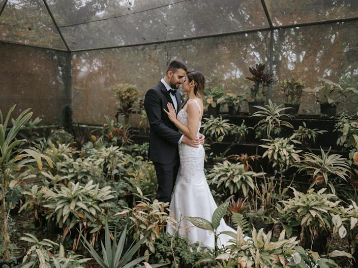 A bride and groom embrace in a green house.