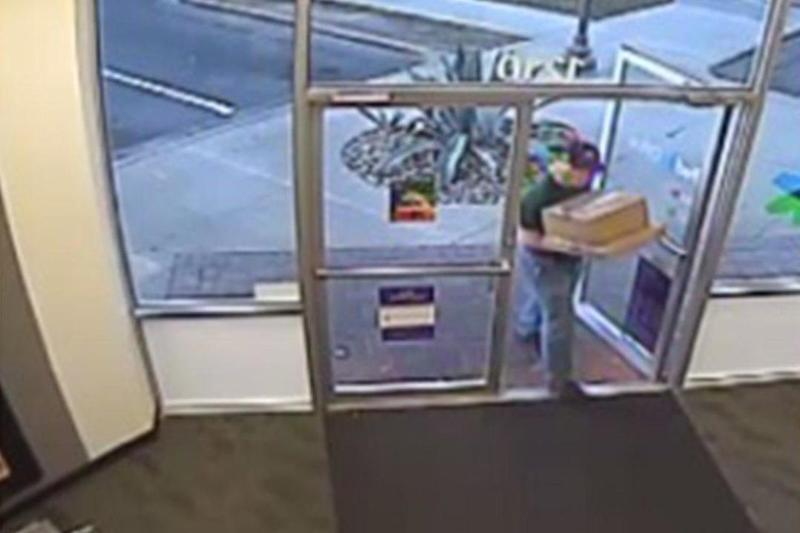 The suspect was shown delivering packages, possibly dressed in a wig ()