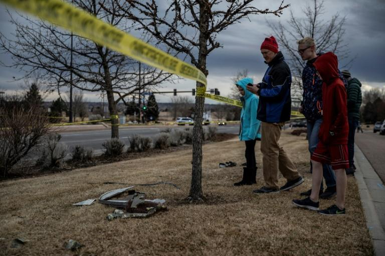 Residents inspect damage from debris fallen from a United Airlines airplane's engine in Broomfield, outside Denver, Colorado, on February 20, 2021