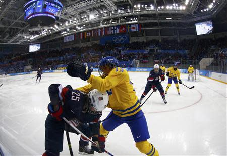 Team USA's Alex Carpenter (25) and Sweden's Lina Wester battle for the puck during the second period of their women's semi-final ice hockey game at the Sochi 2014 Winter Olympic Games, February 17, 2014. REUTERS/Mark Blinch