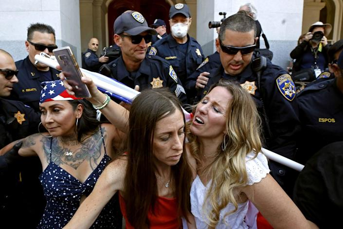 Denise Aguilar, far left, and Tara Thornton, right, huddle together as they are detained by California Highway Patrol.