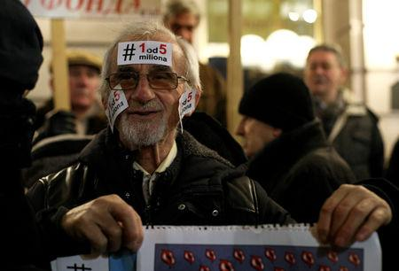 A demonstrator holds a placard during a protest against Serbian President Aleksandar Vucic and his government in central Belgrade, Serbia, January 12, 2019. REUTERS/Djordje Kojadinovic