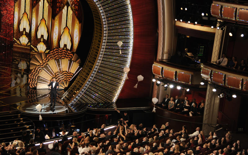 FILE - In this Feb. 26, 2017 file photo, host Jimmy Kimmel speaks as donuts fall onto the audience at the Oscars in Los Angeles. Cameras never find an empty seat at the Academy Awards, with a troop of seat-fillers at the ready to occupy any chair vacated by a bathroom- or bar-bound guest. A parade of extras in tuxedoes and gowns arrive hours before the show begins and are ready to swoop in and sit once the cameras start rolling. (Photo by Chris Pizzello/Invision/AP, File)
