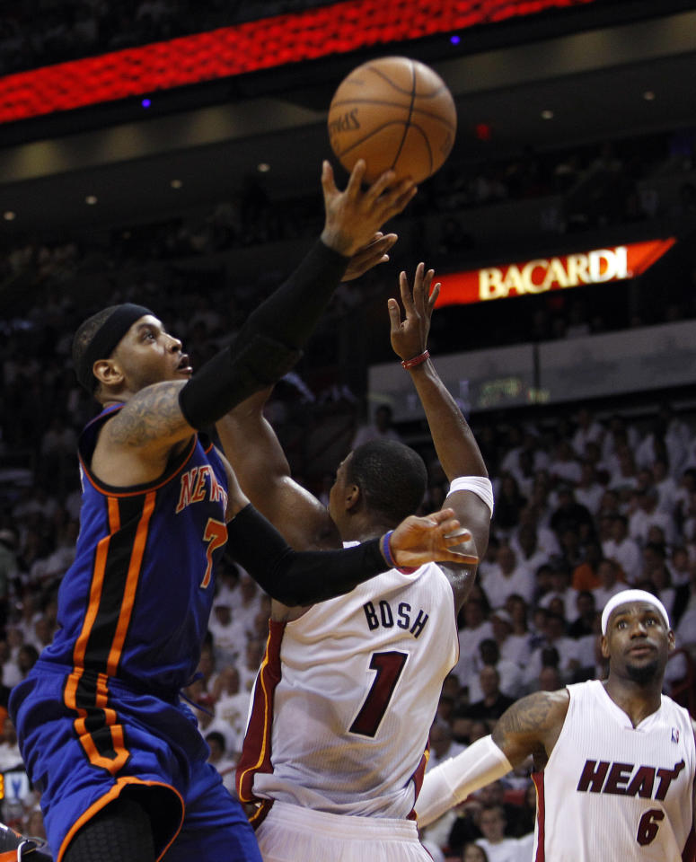 New York Knicks' Carmelo Anthony, left, shoots past Miami Heat's Chris Bosh (1) as Miami Heat's LeBron James (6) looks on in the second half during an NBA basketball game in the first round of the Eastern Conference playoffs in Miami, Saturday, April 28, 2012. (AP Photo/Lynne Sladky)