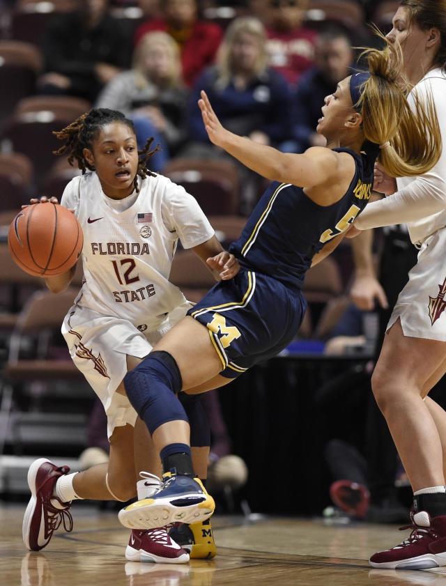 Florida State's Nicki Ekhomu, left, fouls Michigan's Kayla Robbins in the first half of an NCAA college basketball game, Sunday, Dec. 22, 2019, in Uncasville, Conn. (AP Photo/Jessica Hill)