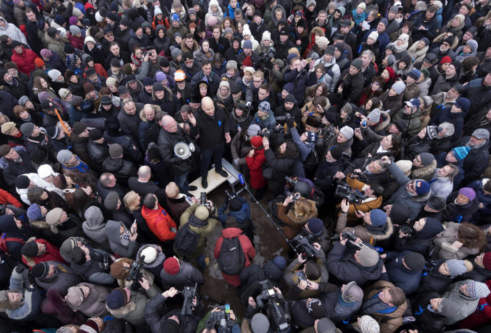 FILE - In this Saturday, Jan. 28, 2017 file photo, Andrei Pivovarov, center, speaks during a protest rally against the transfer of St. Isaac's Cathedral to the Russian Orthodox Church in St.Petersburg, Russia. Russian authorities are ramping up their pressure on dissent ahead of the country's parliamentary election, arresting one opposition activist and raiding several others' homes. Pivovarov has been pulled off a plane at St. Petersburg's airport and is to be taken to Krasnodar in southern Russia on Tuesday, June 1, 2021. (AP Photo/Dmitri Lovetsky, file)