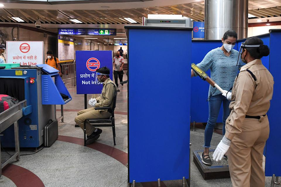 A security personnel searches a woman as she arrives at a metro station after Delhi Metro Rail Corporation (DMRC) resumed services in New Delhi on September 7, 2020. (Photo by PRAKASH SINGH/AFP via Getty Images)