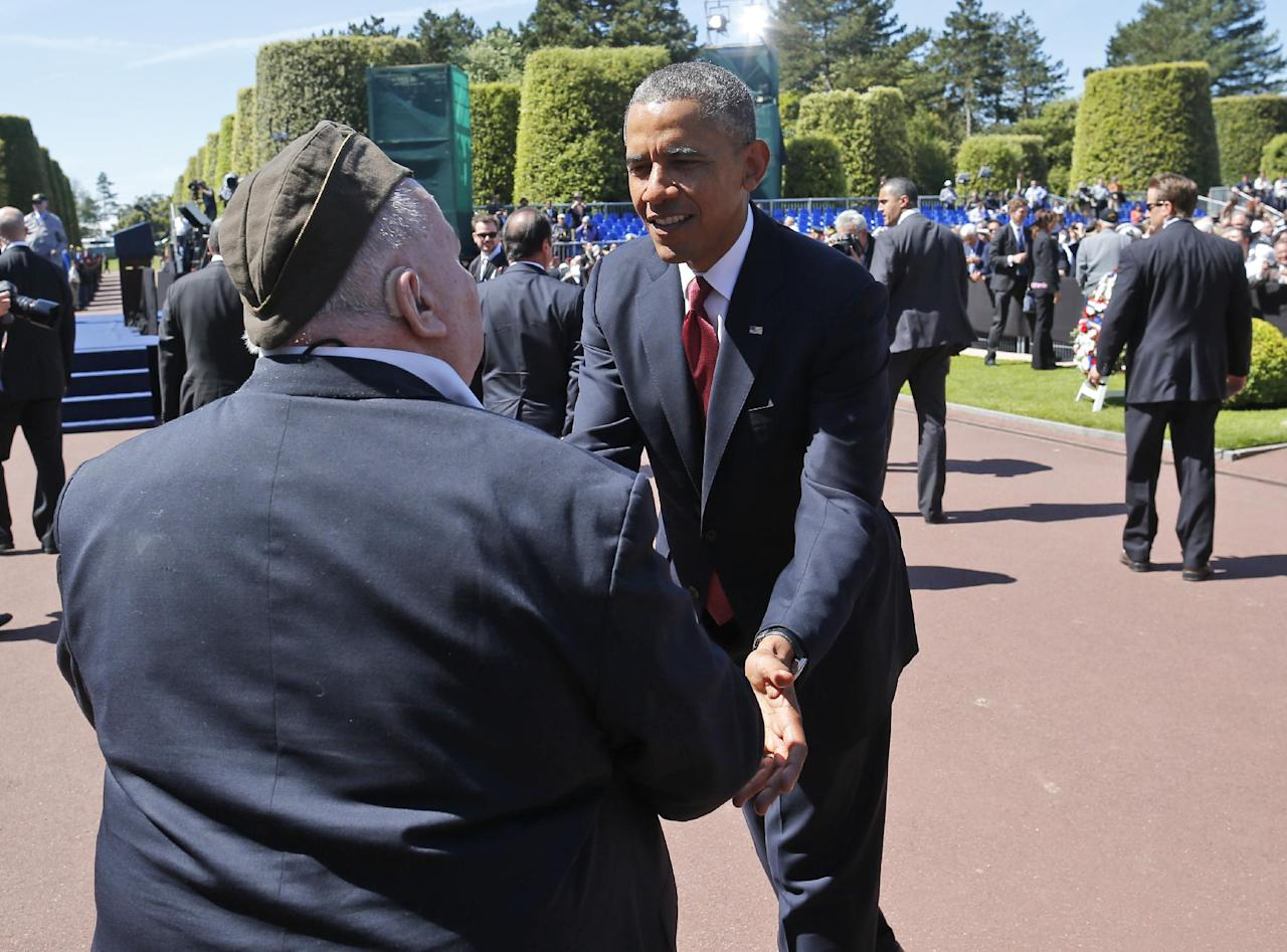 U.S. President Barack Obama greets a veteran at Normandy American Cemetery at Omaha Beach as he participates in the 70th anniversary of D-Day in Colleville sur Mer in Normandy, France, Friday, June 6, 2014. (AP Photo/Charles Dharapak)