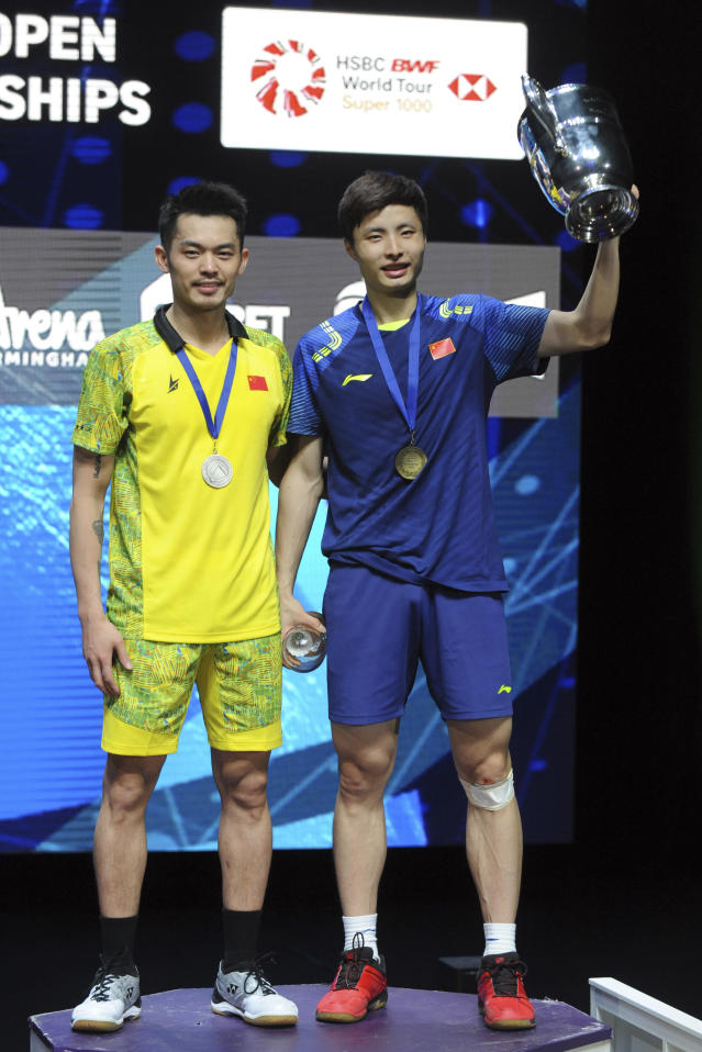Winner China's Shi Yuqi, right, and second placed Lin Dan, also from China, stand on the podium after the men's singles final match at the All England Open Badminton tournament in Birmingham, England, Sunday March 18, 2018. (AP Photo/Rui Vieira)