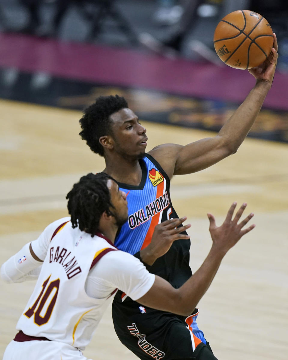 Oklahoma City Thunder's Hamidou Diallo, right, drives to the basket against Cleveland Cavaliers' Darius Garland during the second half of an NBA basketball game Sunday, Feb. 21, 2021, in Cleveland. (AP Photo/Tony Dejak)