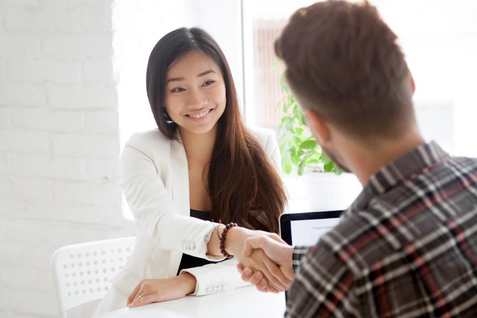 Back view of male hr shaking hand of smiling Asian job candidate, greeting with successful interview, female employee handshaking supervisor, making good first impression. Employment, hiring concept