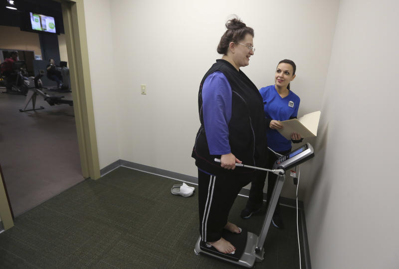 Personal trainer Krisaane Hale, right, weights Ellen Hays for a body mass index reading before working out in a morning exercise class at the Downsize Fitness gym in Addison, Texas, Thursday, Jan. 3, 2013. Downsize Fitness is a selective gym where the rule is that new members must tip the scales. New members are weighed and have their body mass index measured. (AP Photo/LM Otero)