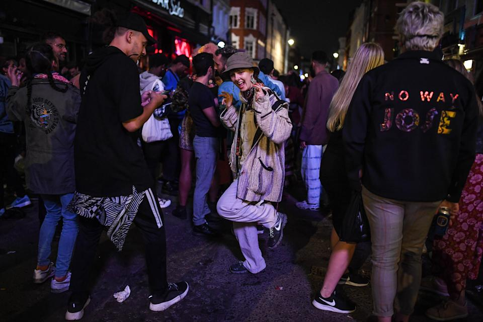 LONDON, ENGLAND - JULY 04: A woman is seen dancing outside a pub in Soho on July 4, 2020 in London, United Kingdom. The UK Government announced that Pubs, Hotels and Restaurants can open from Saturday, July 4th providing they follow guidelines on social distancing and sanitising. (Photo by Peter Summers/Getty Images)