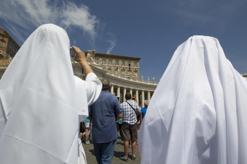 Nuns watch Pope Francis as he blesses the faithful during the Angelus noon prayer he celebrated from the window of his studio overlooking St. Peter's Square, at the Vatican, Sunday, July 21, 2013. Francis leaves Monday, July 22, for Rio de Janeiro, where a million or more young Catholics are expected to celebrate the World Youth Day with their new pope. The trip is the first international journey for the 76-year-old Argentine since he became pope in March. (AP Photo/Andrew Medichini)